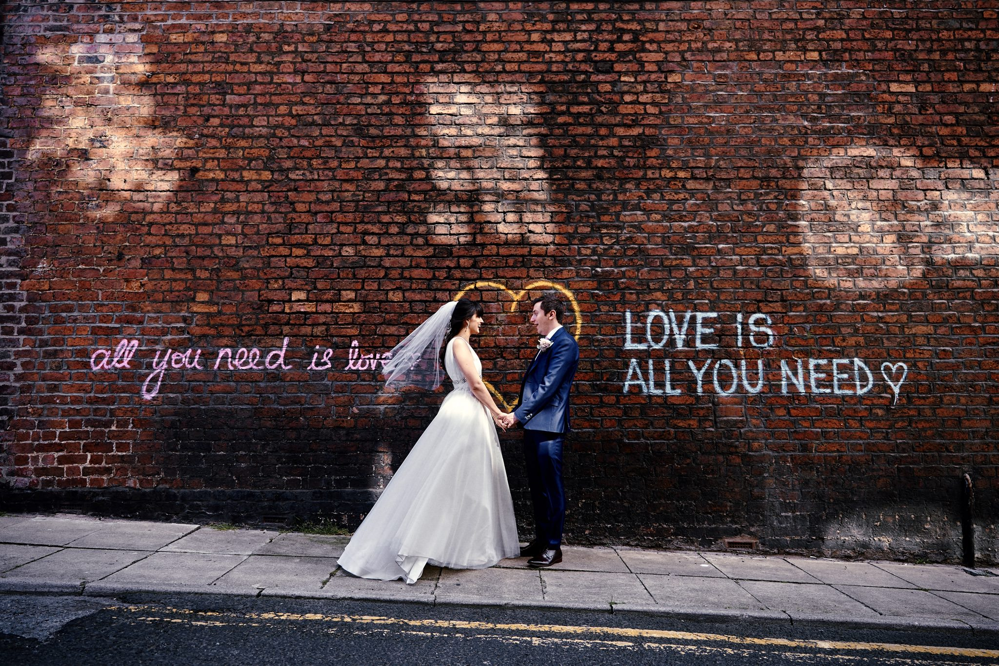 All you need is love, Love is all you need! Graffiti on Wall in Liverpool with Bride and Groom