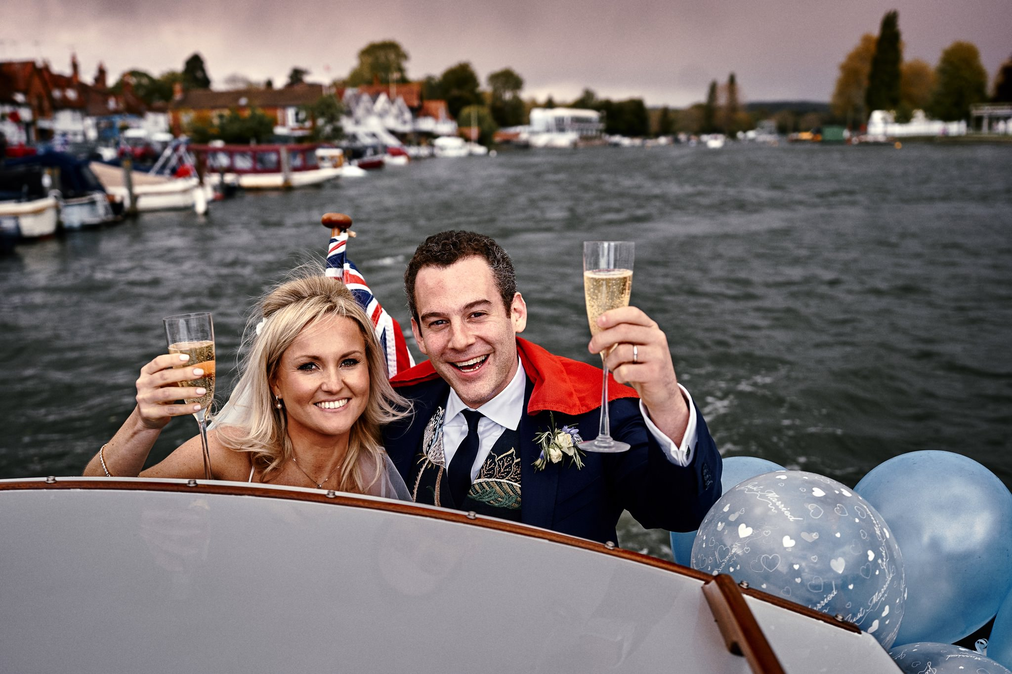 Bride and groom celebrate after their wedding on a boat on their way to Temple Island, Henley-on-Thames