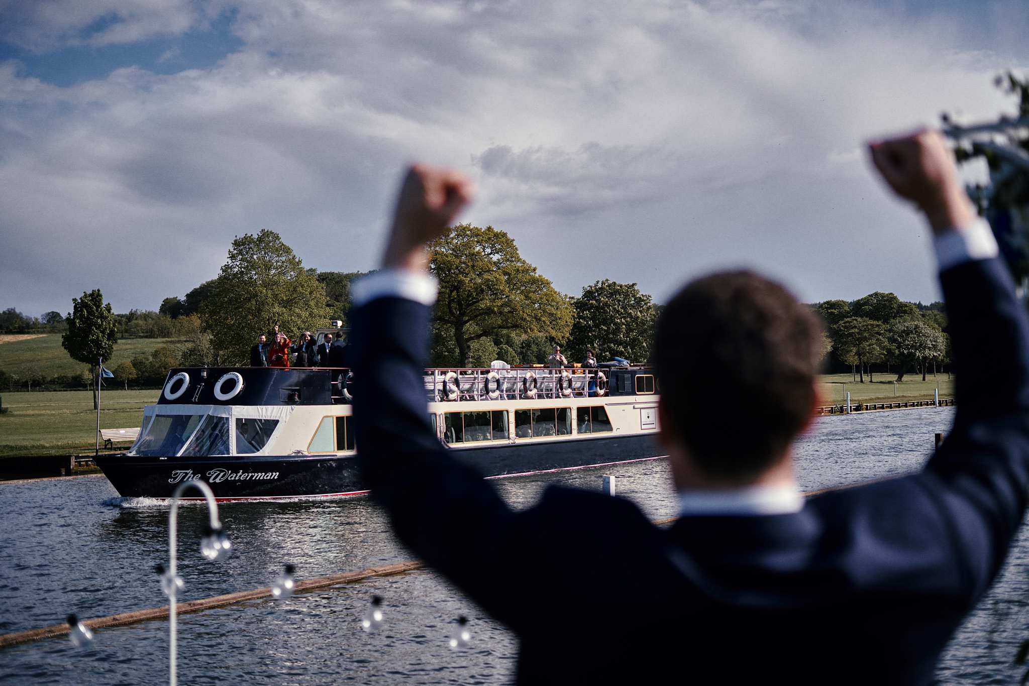 Groom welcomes wedding guests arriving on boat
