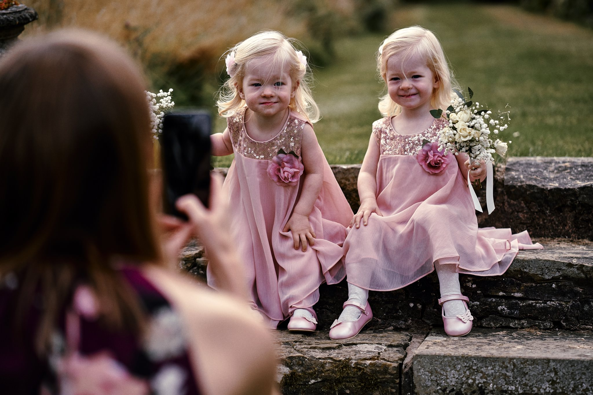 Twin girls pose for a quick photo during a wedding reception at Walcot Hall Hotel, Shropshire.