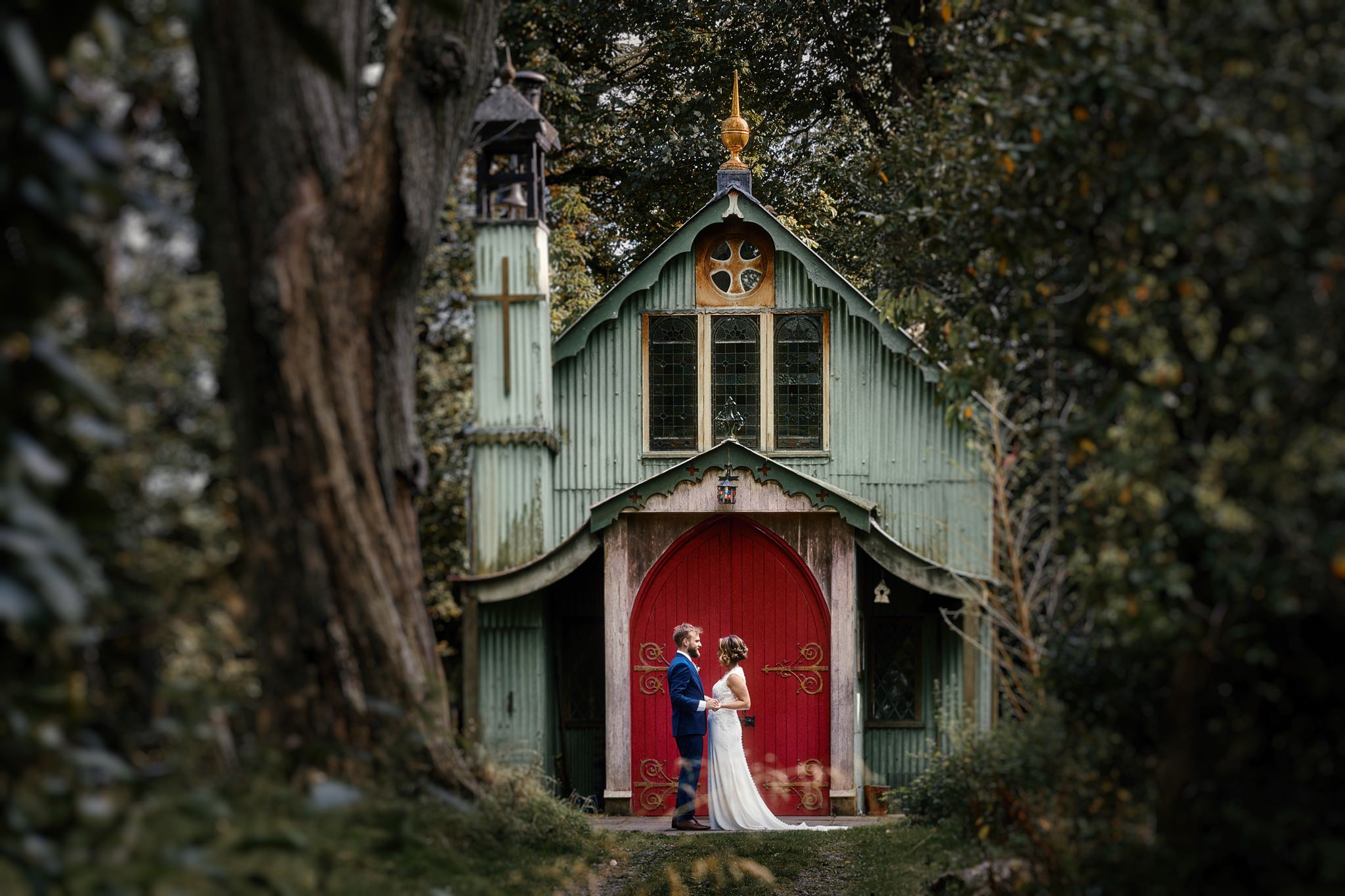 Bride and groom pose in the doorway of the tin tabernacle at Walcot Hall Hotel, Shropshire.