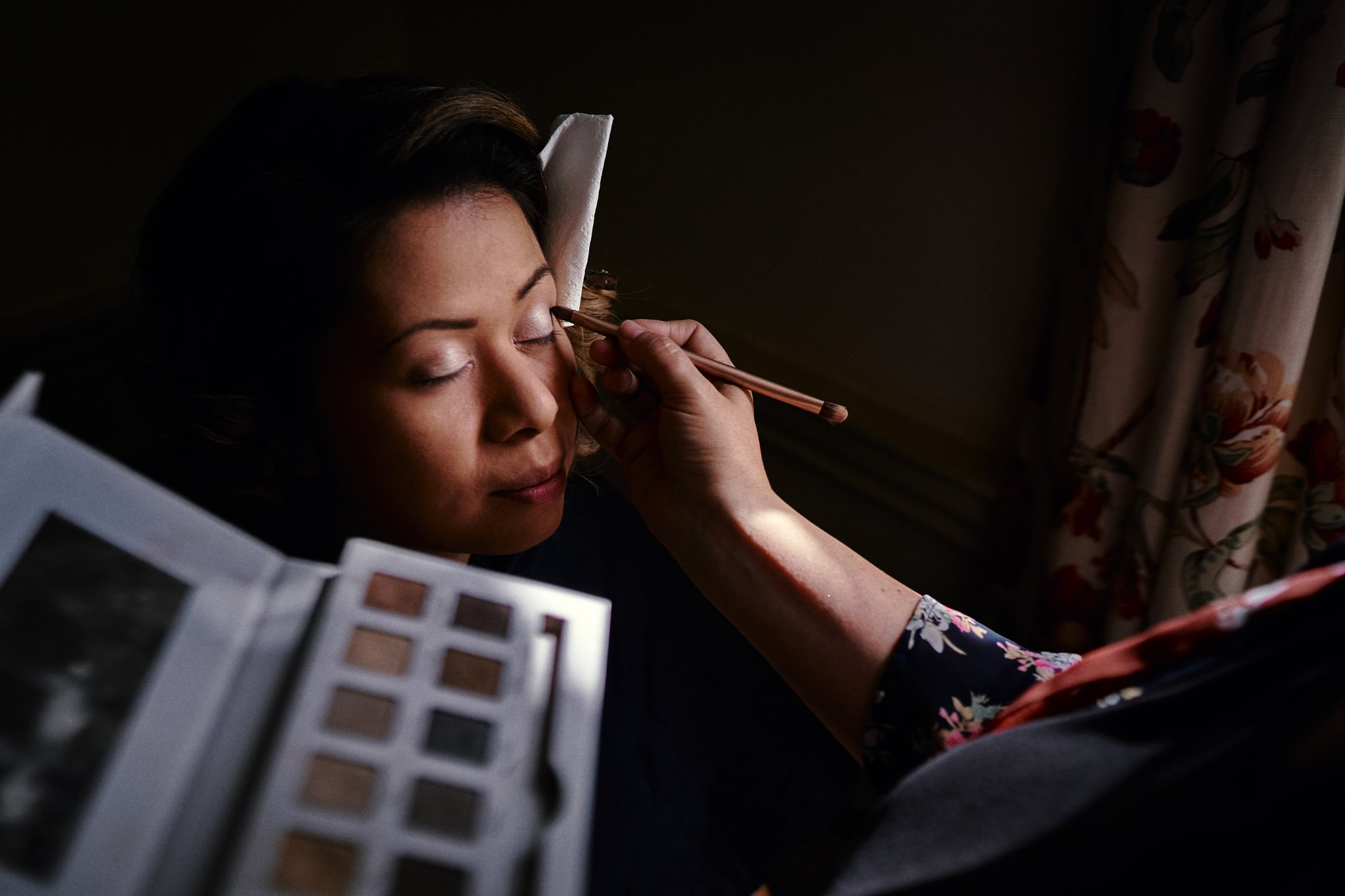 Bride having her makeup done during bridal prep at Walcot Hall Hotel, Shropshire.