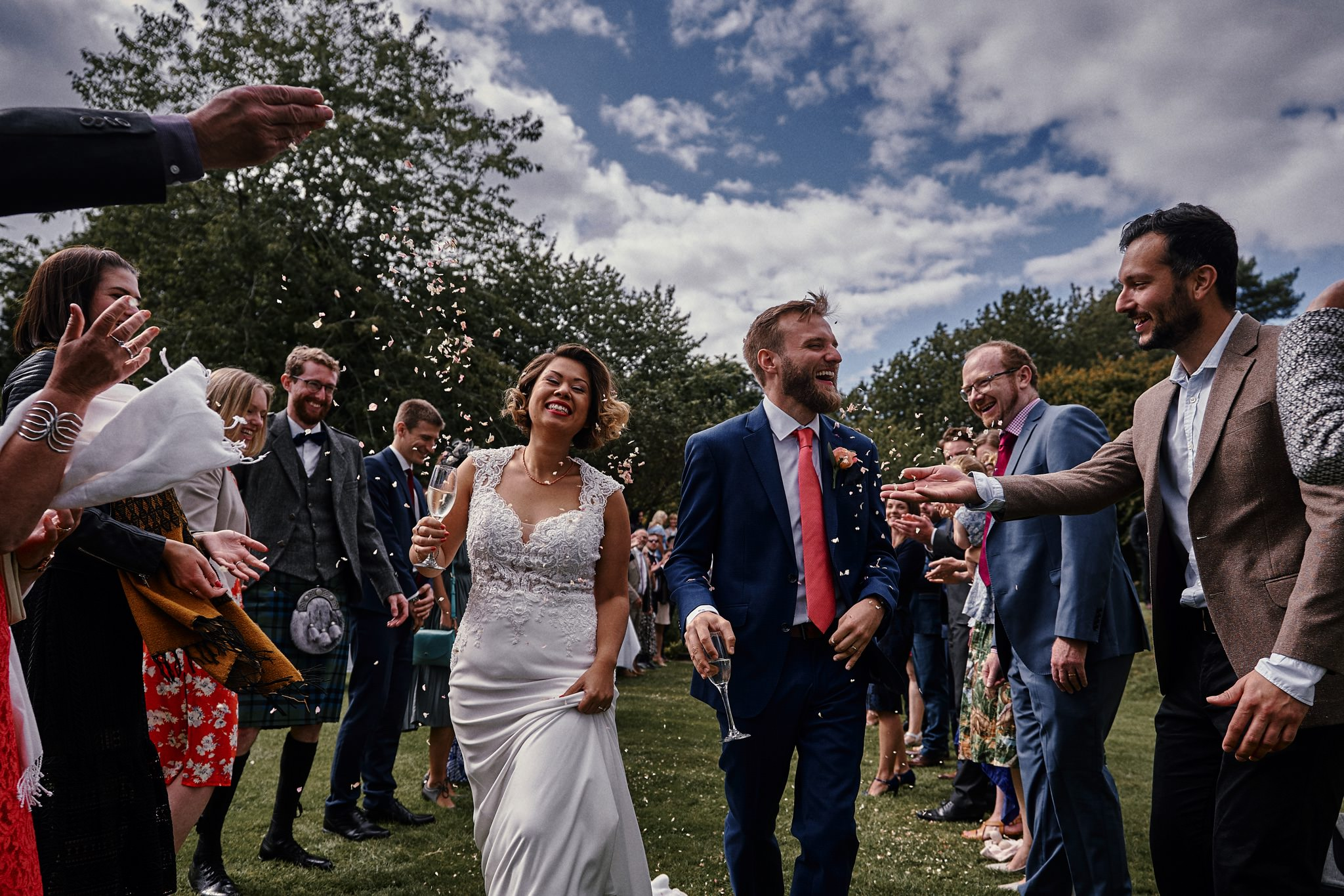 Bride and groom dodge confetti in the beautiful gardens at Walcott Hall Hotel, Shropshire.