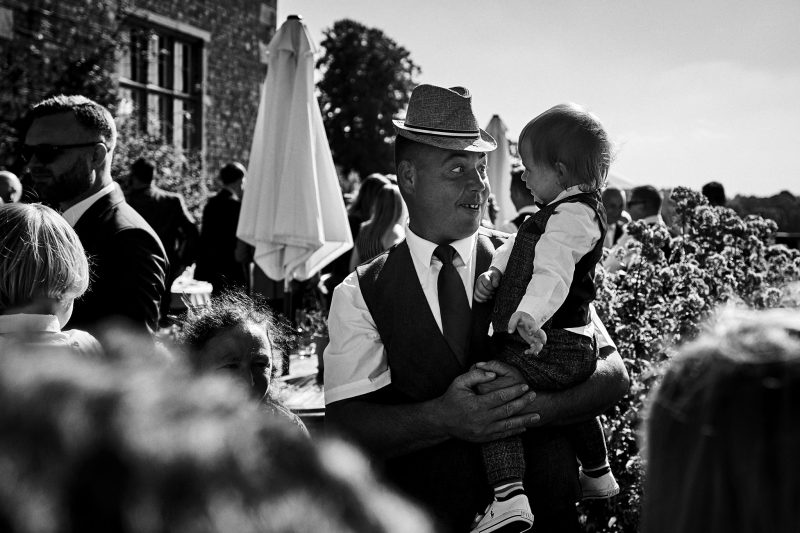 Father pulling funny face for son at Wedding