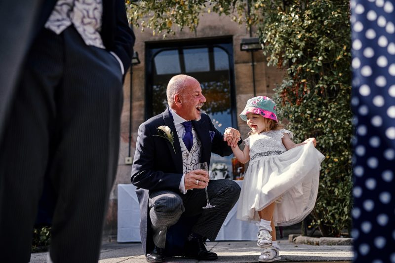 Groom laughing with his flower girl grand-daughter