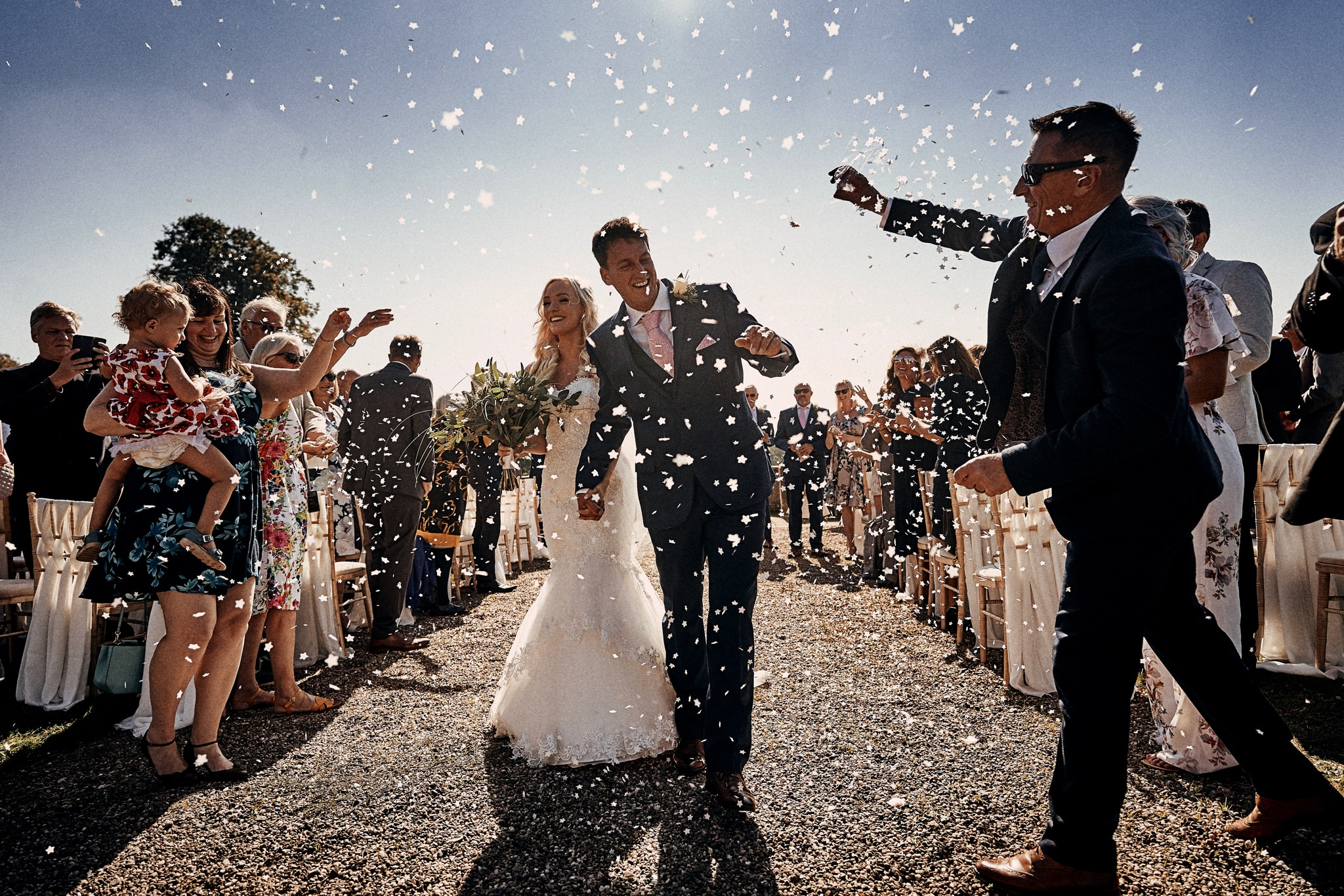 Bride and groom dodge confetti after their wedding